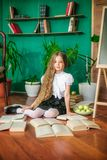 A sweet schoolgirl of junior classes with long blond hair with books, a school board and apples royalty free stock photos
