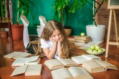 A sweet schoolgirl of junior classes with long blond hair with books, a school board and apples stock image