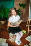 A sweet schoolgirl of junior classes with long blond hair with books, a school board and apples stock photo