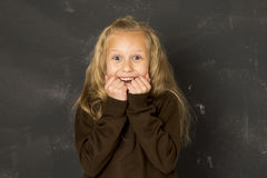 Sweet schoolgirl in uniform laughing excited in front of school class blackboard smiling happy. Young beautiful blond sweet schoolgirl in uniform laughing Stock Photos