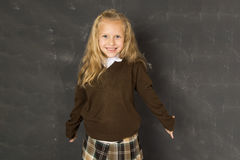 Sweet schoolgirl in uniform laughing excited in front of school class blackboard smiling happy. Young beautiful blond sweet schoolgirl in uniform laughing Royalty Free Stock Images