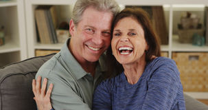Sweet senior couple cuddling on couch. Laughing stock images