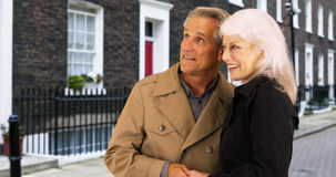 Sweet senior couple embracing each other for warmth while waiting for a ride Stock Photography