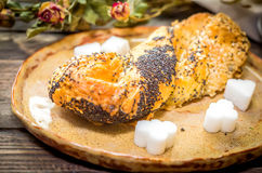 Sweet sesame bun on a rustic clay plate Stock Image