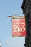 Sweet shop sign. A framed red sign board with 'Traditional Sweet Shop' written in beige suspended on a hanger from a stone wall Royalty Free Stock Image