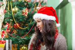 Sweet shy young woman in Santa hat smiling looking aside Stock Photography