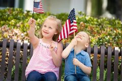 Sweet Sister and Brother Playing with American Flags. Young Sister and Brother Comparing Each Others American Flag Size On The Bench At The Park Royalty Free Stock Photo