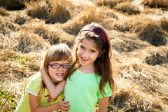 Sweet Sisters In Front of Crushed Dry Reeds Royalty Free Stock Photos