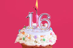 Sweet sixteen. Birthday celebration. Bright pink background and a cupcake with a candle Royalty Free Stock Photo