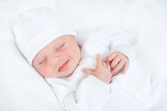 Sweet sleeping newborn baby in a white hat Royalty Free Stock Image