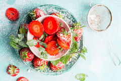 Sweet sliced  Strawberries in bowls with icing sugar on light blue background Stock Photo