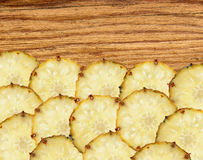 Sweet slices of pineapple fruit on wooden background Stock Images