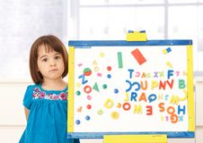 Sweet small girl standing at drawing board. Portrait of sweet small girl standing at drawing board full of letters and numbers, looking at camera Stock Photos