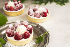 Sweet small tarts with fresh raspberry. Sweet small french tarts with fresh raspberry and cream over vintage stone table Stock Images
