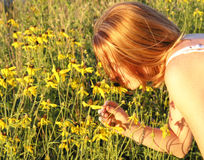 Sweet Smell. A young red headed woman stoops to smell a yellow wild flower in a park outdoors.  The sun is setting, and warms the picture Royalty Free Stock Image