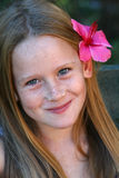 Sweet smile. A white caucasian girl child smiling with a flower in her hair Royalty Free Stock Image