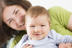 Sweet smiling baby boy laughing together with his mother. stock image
