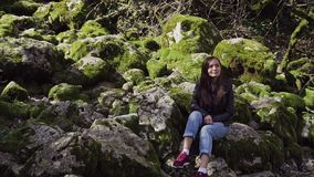 Sweet smiling girl is sitting among scattered large stones which are covered with green moss. A sweet smiling girl is sitting among scattered large stones which stock video