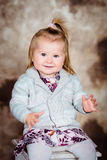 Sweet smiling little girl with blond hair sitting on chair Royalty Free Stock Photo