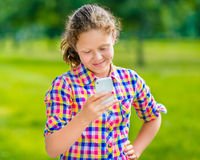 Sweet smiling teenage girl in casual clothes with smartphone. In her hand, looking at screen, reading a message, using Facebook in sunny day in summer park stock images