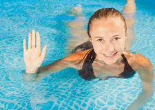 Sweet smiling young girl swimming in the pool Stock Image