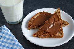 Sweet snack with chocolate spread and milk. Slice of bread with chocolate cream and a glass of milk Royalty Free Stock Image