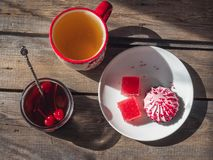 Sweet snack with cranberry marshmallow and marmalade, tea in a large ceramic mug and a glass jar with cherry jam and a. A sweet snack with cranberry marshmallow royalty free stock image