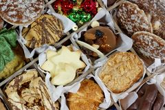 Sweet Sorted Christmas Goodies Closeup. Selection of Christmas cookies with some Christmas ornaments sorted in a sectioned box closeup stock photo