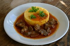 Sweet and sour beef liver with polenta Royalty Free Stock Photos