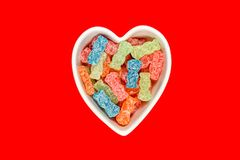 Sweet and Sour Candy Sugar Junk Food. Variety of different color sweet and sour candy or sugar junk food in a heart shaped bowl royalty free stock photography
