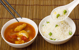 Sweet and Sour Chicken. A bowl of spicy sweet and sour chicken and a bowl of egg fried rice Royalty Free Stock Images