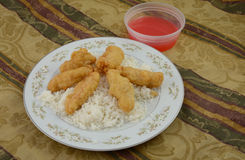 Sweet and sour chicken with white rice and sauce on plate. On tablecloth Stock Photo