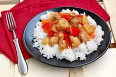 Sweet and sour food with rice,red pepper,pineapple,onion and chicken meat on red cloth on black plate on wooden background Stock Photo