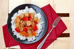 Sweet and sour food with rice,red pepper,pineapple,onion and chicken meat on red cloth on black plate on wooden background Royalty Free Stock Images