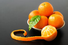 Sweet sour peeled tangerine orange and leaf on plate  Royalty Free Stock Images