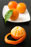 Sweet sour peeled tangerine orange and leaf on plate. Sweet sour peeled tangerine orange on plate and leaf on gray black dark background Stock Image