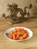Sweet and sour pork and dragon curio. Chinese dish sweet and sour pork and dragon carving curio Stock Photography