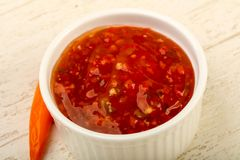 Sweet and sour sauce. In the bowl over wooden background Stock Photography