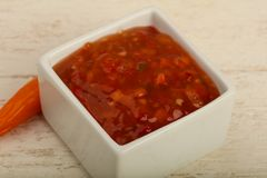 Sweet and sour sauce. In the bowl over wooden background Royalty Free Stock Photo