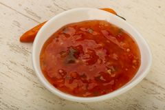 Sweet and sour sauce. In the bowl over wooden background Stock Images