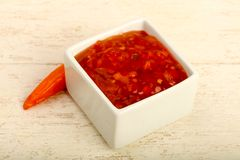 Sweet and sour sauce. In the bowl over wooden background Royalty Free Stock Photography