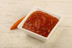Sweet and sour sauce. In the bowl over wooden background Royalty Free Stock Photos