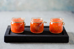 Sweet sour sauce with vegetable pieces. On a black board Royalty Free Stock Images