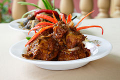 Sweet Spicy Chicken. A plate of sweet chili chicken with garnishing, a Malaysian cuisine, with another dish in the background Stock Photos