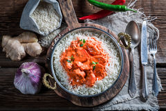 Sweet and spicy tikka masala with chicken in tomato sauce. On old wooden table Stock Photo
