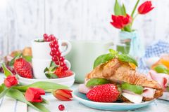 Sweet spring breakfast with croissants and bacon on a light background. A bouquet of red tulips and fresh berries of strawberries. And currants. The concept of stock image