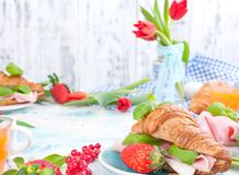 Sweet spring breakfast with croissants and bacon on a light background. A bouquet of red tulips and fresh berries of strawberries. And currants. The concept of royalty free stock photos