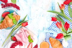 Sweet spring breakfast with croissants and bacon on a light background. A bouquet of red tulips and fresh berries of strawberries. And currants. The concept of royalty free stock image