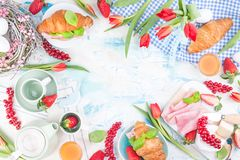 Sweet spring breakfast with croissants and bacon on a light background. A bouquet of red tulips and fresh berries of strawberries. And currants. The concept of stock photos