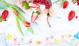 Sweet spring breakfast with croissants and bacon on a light background. A bouquet of red tulips and fresh berries of strawberries. And currants. The concept of stock photo